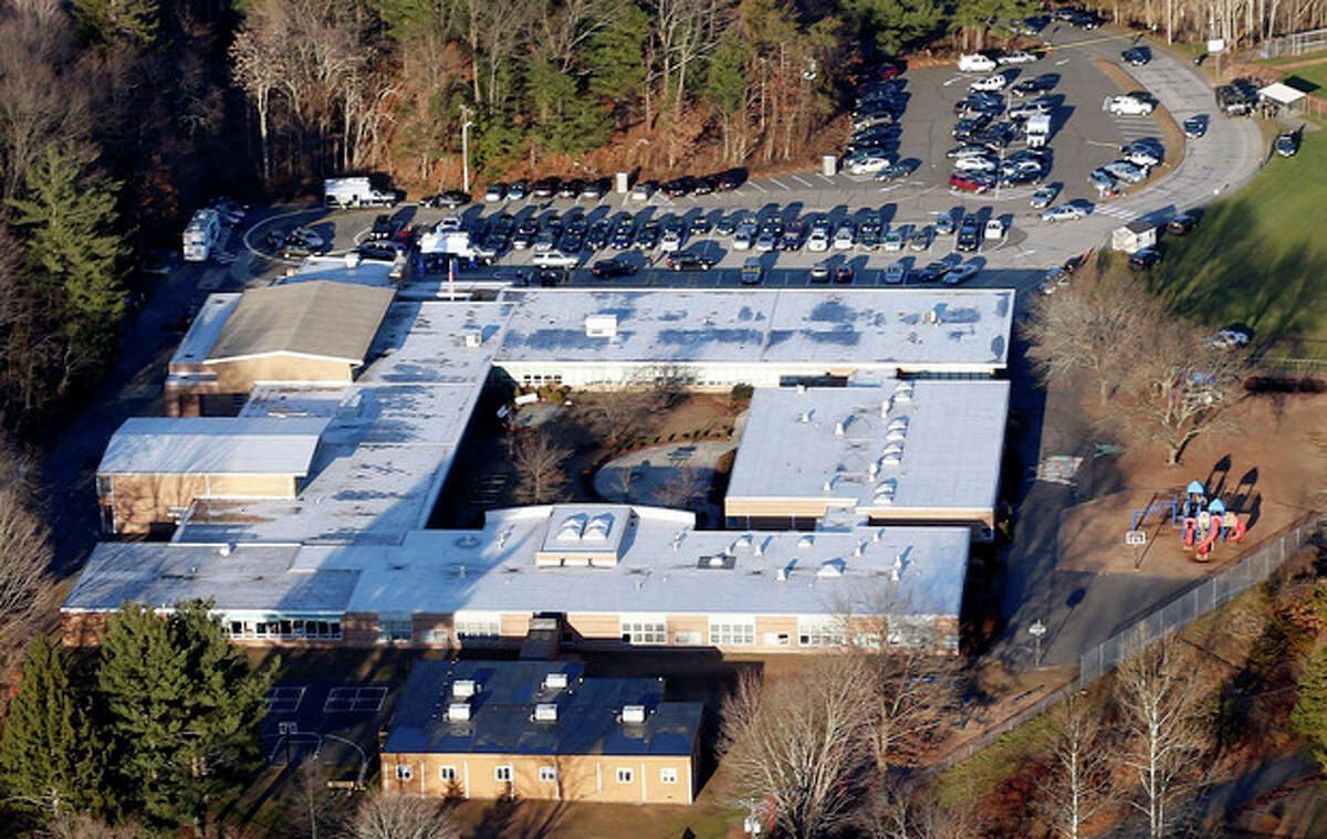 FILE - This Dec. 14, 2012 aerial file photo shows Sandy Hook Elementary School in Newtown, Conn., where a gunman shot 26 people dead. The dispatchers at the Newtown Emergency Communications Center have won praise from officials and colleagues around the country for their role in the response to the shooting. The call center director said the staff has been lifted by the outpouring of support as the dispatchers recover emotionally, along with the community that still peppers them with calls over anything out of the ordinary. (AP Photo/Julio Cortez, File)