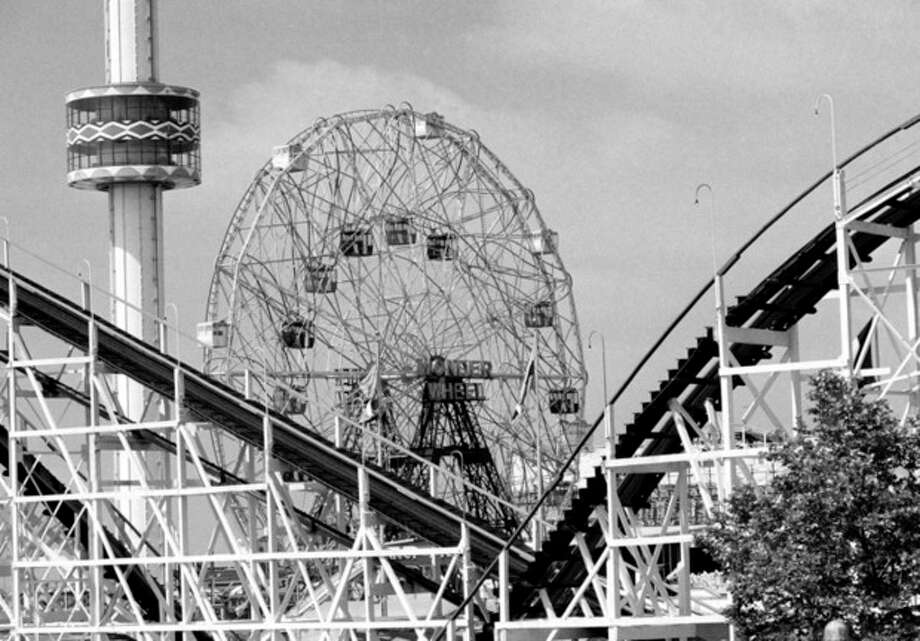 FILE- In this June 30, 1977 file photo, the 275-foot tall Astrotower , left, reaches into the sky along with the 150-foot-tall Wonder Wheel, and the Cyclone roller coaster snakes through the foreground at the Astorland amusement park in the Coney Island section of the Brooklyn borough of New York. The iconic Coney Island amusement park was evacuated, Tuesday, July 2, 2013 after reports that the Astrotower observation tower was swaying in the wind. (AP Photo, File) / AP