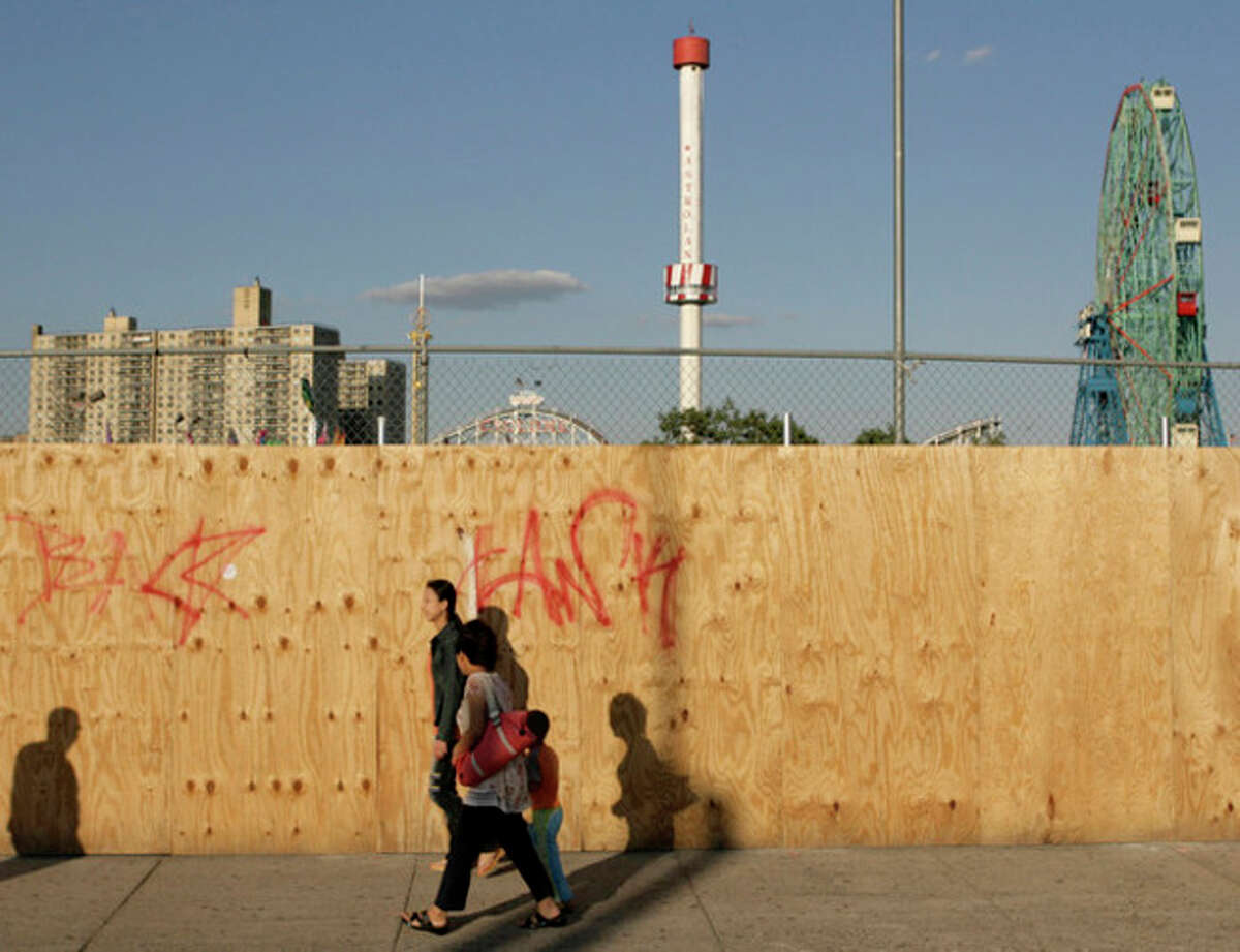 FILE- In this June 6, 2007 file photo, pedestrians walk past a boarded up section of the Coney Island amusement district in the Brooklyn borough of New York with the Astrotower rising in the background. The iconic Coney Island amusement park was evacuated, Tuesday, July 2, 2013 after reports that the 275-foot tall Astrotower observation tower was swaying in the wind. (AP Photo/Seth Wenig, FIle)