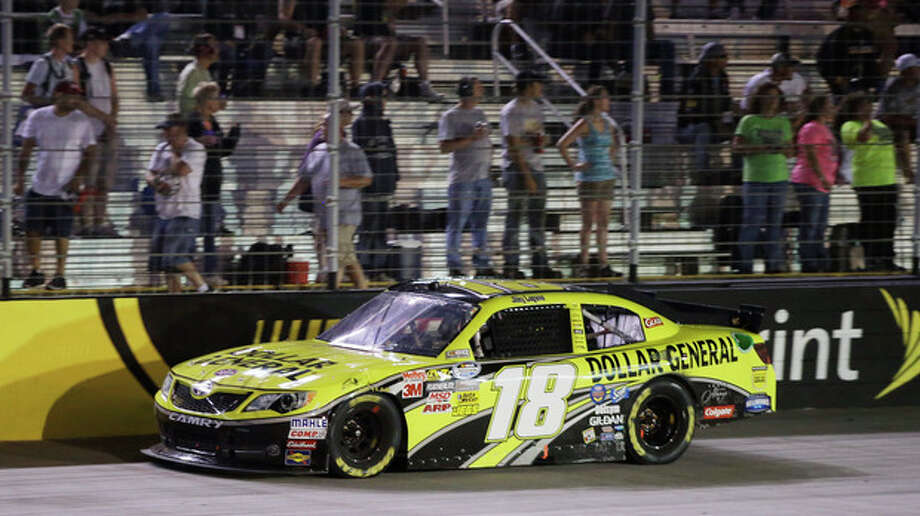 Joey Logano drives past fans on his way to winning the Food City 250 NASCAR Nationwide Series auto race on Friday, Aug. 24, 2012, in Bristol, Tenn. (AP Photo/Mark Humphrey) / AP