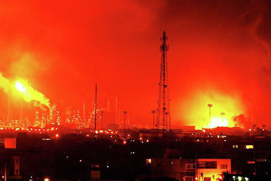 Fire rises over Amuay refinery near Punto Fijo, Venezuela, Saturday, Aug. 25, 2012. A huge explosion rocked Venezuela's biggest oil refinery, killing at least 19 people and injuring dozens, an official said. (AP Photo/Daniela Primera) / AP