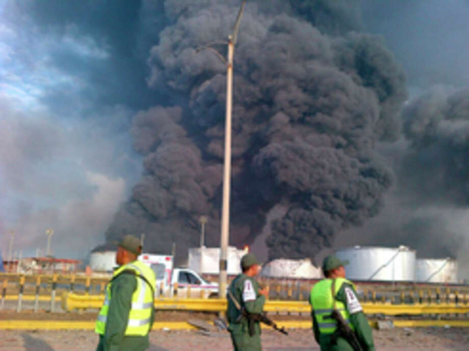 Large plumes of smoke rise from the Amuay refinery as national guards soldiers watch near Punto Fijo, Venezuela, Saturday, Aug. 25, 2012. A huge explosion rocked Venezuela's biggest oil refinery, killing and injuring dozens, an official said. (AP Photo/Abisaid Cermeno) / AP
