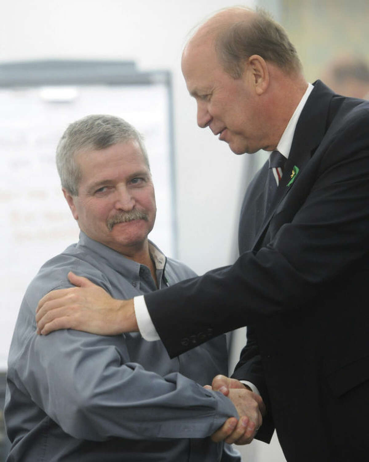 In this April 17, 2013 photo, Robert Nute, left, is congratulated by Newtown Police Chief Michael Kehoe after winning an emergency telecommunications award, at the Newtown Municipal Center in Newtown, Conn. Nute, of the Newtown Emergency Communications Center, handled dispatch calls during the Sandy Hook Elementary School shooting on Dec. 14, 2012. The dispatchers at the Newtown center have won praise from officials and colleagues around the country for their role in the response to the shooting. The call center director said the staff has been lifted by the outpouring of support as the dispatchers recover emotionally, along with the community that still peppers them with calls over anything out of the ordinary. (AP Photo/The News-Times, Tyler Sizemore) MANDATORY CREDIT