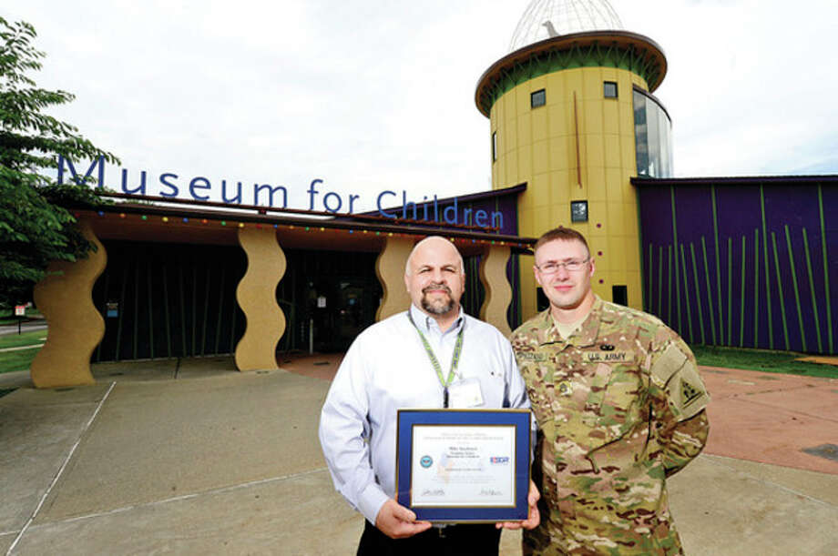 Hour photo / Erik TrautmannReturning Army Reserve Sgt. Scott Spezzano honored his former employers at Stepping Stones Museum for Children including Director of Facilities Mike Jacabacci after serving in Afghanistan. / (C)2013, The Hour Newspapers, all rights reserved