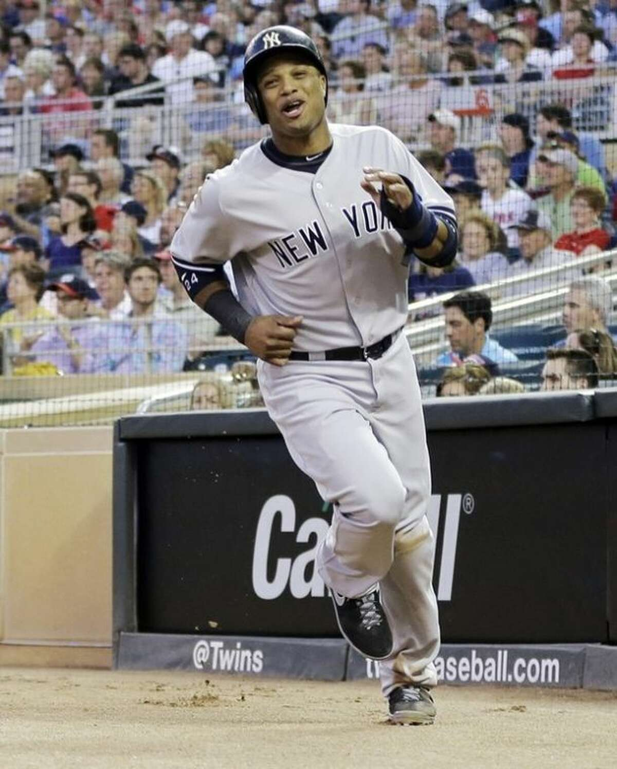 New York Yankees' Robinson Cano races to the dugout after scoring the go-ahead run on a sacrifice fly by Lyle Overbay off Minnesota Twins pitcher Caleb Thielbar in the sixth inning of a baseball game on Wednesday, July 3, 2013, in Minneapolis. (AP Photo/Jim Mone)