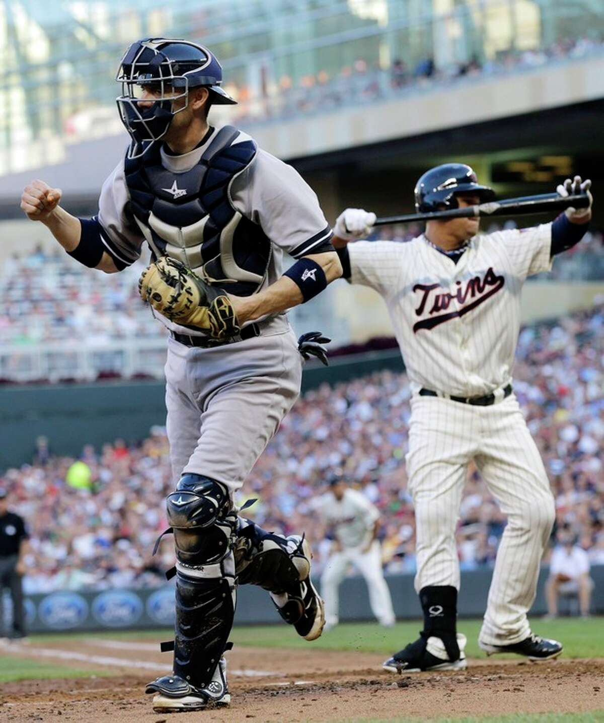 5New York Yankees catcher Chris Stewart, left, pumps his fist after Minnesota Twins' Oswaldo Arcia, right, struck out to CC Sabathia in the third inning of a baseball game on Wednesday, July 3, 2013, in Minneapolis. (AP Photo/Jim Mone)