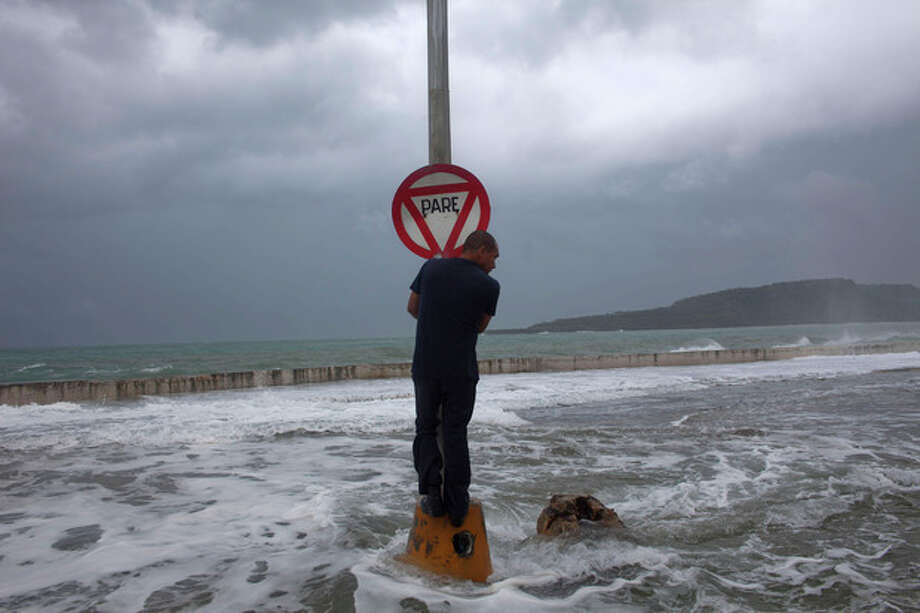 A man stands on a post with a stop sign as waves pass the seawall during the passage of Tropical Storm Isaac in Baracoa, Cuba, Saturday, Aug. 25, 2012. Tropical Storm Isaac pushed into Cuba on Saturday after sweeping across Haiti's southern peninsula. Isaac's center made landfall just before midday near the far-eastern tip of Cuba. (AP Photo/Ramon Espinosa) / AP