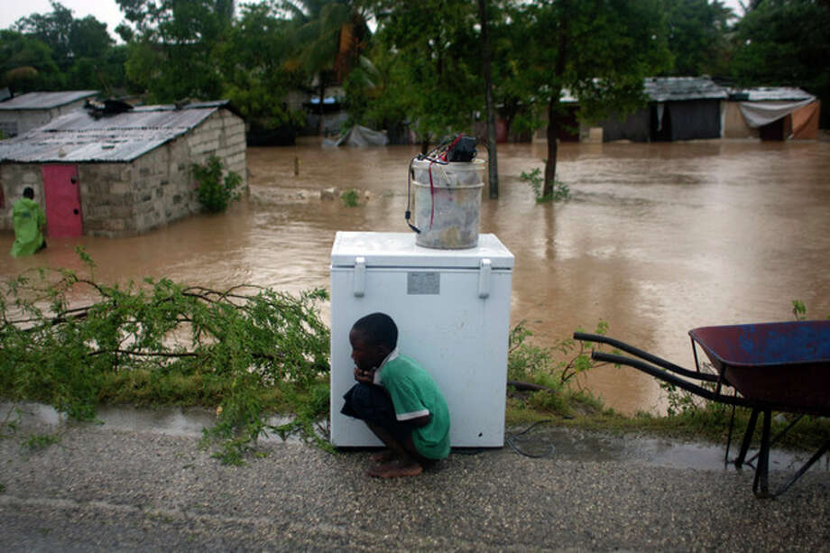 A boy tries to take cover from the cold behind an appliance sitting higher than the floodwaters triggered by Tropical Storm Isaac in Port-au-Prince, Haiti, Saturday Aug. 25, 2012. Tropical Storm Isaac swept across Haiti's southern peninsula early Saturday, dousing a capital city prone to flooding and adding to the misery of a poor nation still trying to recover from the 2010 earthquake. (AP Photo/Dieu Nalio Chery) / AP