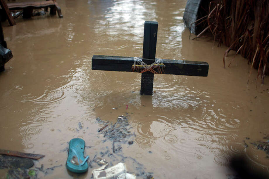 A voodoo cross in honor of the Baron Samedi stands in floodwaters, triggered by Tropical Storm Isaac, at a place of worship in Port-au-Prince, Haiti, Saturday, Aug. 25, 2012. Tropical Storm Isaac swept across Haiti's southern peninsula early Saturday, dousing a capital city prone to flooding and adding to the misery of a poor nation still trying to recover from the 2010 earthquake. (AP Photo/Dieu Nalio Chery) / AP