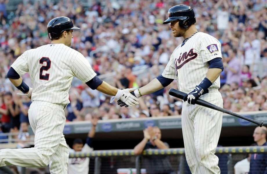 Minnesota Twins' Ryan Doumit, right, congratulates teammate Brian Dozier who scores on an RBI-double by Joe Mauer off New York Yankees pitcher CC Sabathia in the third inning of a baseball game on Wednesday, July 3, 2013, in Minneapolis. (AP Photo/Jim Mone) / AP