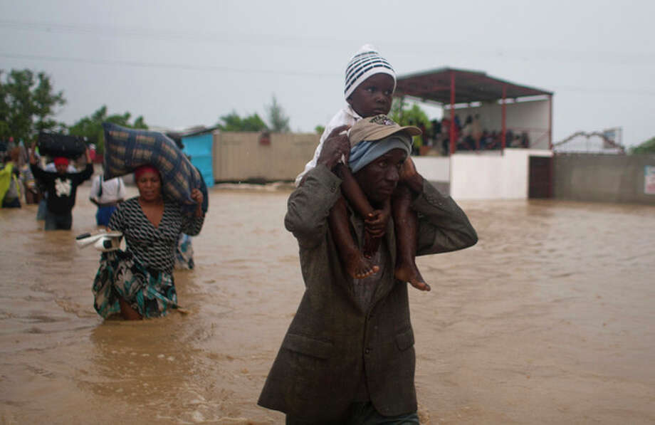 A man carries a child as residents leave an area flooded by Tropical Storm Isaac in Port-au-Prince, Haiti, Saturday, Aug. 25, 2012. Tropical Storm Isaac swept across Haiti's southern peninsula early Saturday, dousing a capital city prone to flooding and adding to the misery of a poor nation still trying to recover from the 2010 earthquake. (AP Photo/Dieu Nalio Chery) / AP