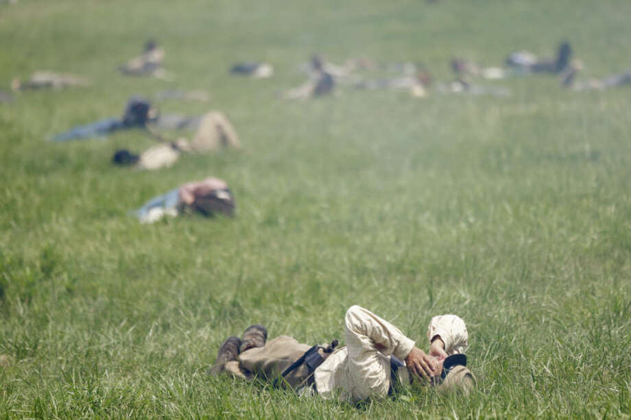 """In this June 30, 2013 file photo, re-enactors demonstrate Pickett's Charge during ongoing activities commemorating the 150th anniversary of the Battle of Gettysburg at Bushey Farm in Gettysburg, Pa. One of the most difficult challenges for any mock general at a Civil War battle re-enactment is deciding which of his men must """"die."""" (AP Photo/Matt Rourke)"""