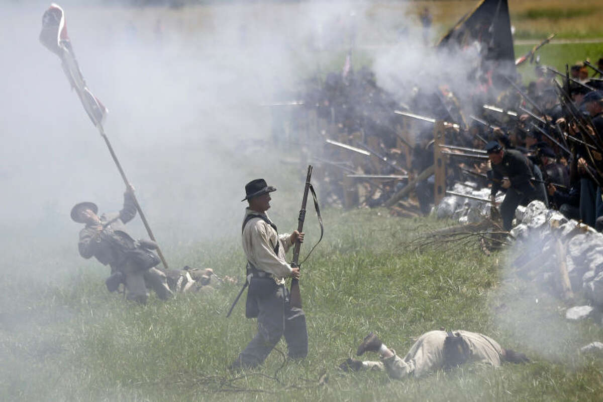 """In this June 30, 2013 file photo, re-enactors portray Pickett's Charge during ongoing activities commemorating the 150th anniversary of the Battle of Gettysburg at Bushey Farm in Gettysburg, Pa. One of the most difficult challenges for any mock general at a Civil War battle re-enactment is deciding which of his men must """"die."""" (AP Photo/Matt Rourke)"""