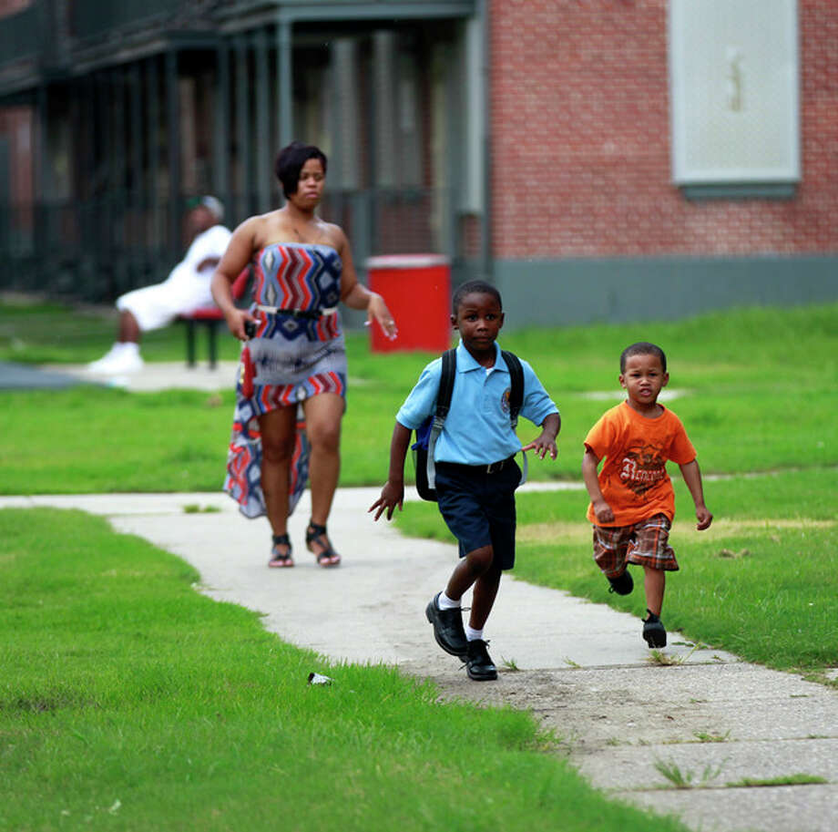 Children run in a courtyard of the Iberville housing projects, slated to be torn down, in New Orleans, Thursday, Aug. 23, 2012. The face of New Orleans is changing: Seven years after Hurricane Katrina the city many said would not recover is racially more diverse, and whiter, younger and richer; indicators not of failure but its success at reinventing itself. In fact, the city is experiencing a boom, and even gentrifying.(AP Photo/Gerald Herbert) / AP