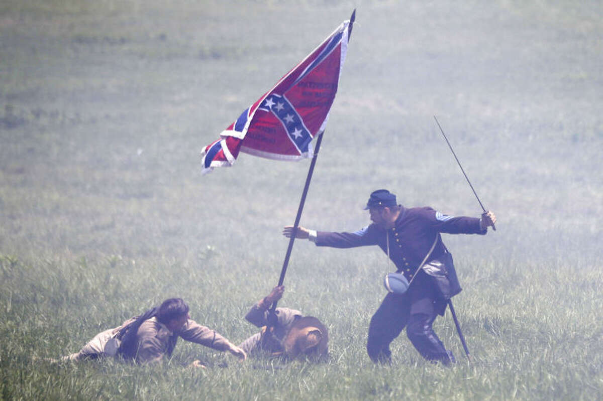 CORRECTS SPELLING OF GREAT IN FIRST SENTENCE - William H. Hincks, right, portrays his great, great, grandfather Medal of Honor recipient William Bliss Hincks taking a Confederate flag from a color bearer portrayed by Skip Koontz, center, of Sharpsburg Md., at a re-enactment of Pickett's Charge during ongoing activities commemorating the 150th anniversary of the Battle of Gettysburg, Sunday, June 30, 2013, at Bushey Farm in Gettysburg, Pa. Union forces turned away a Confederate advance in the pivotal battle of the Civil War fought July 1-3, 1863, which was also the war's bloodiest conflict with more than 51,000 casualties. (AP Photo/Matt Rourke)