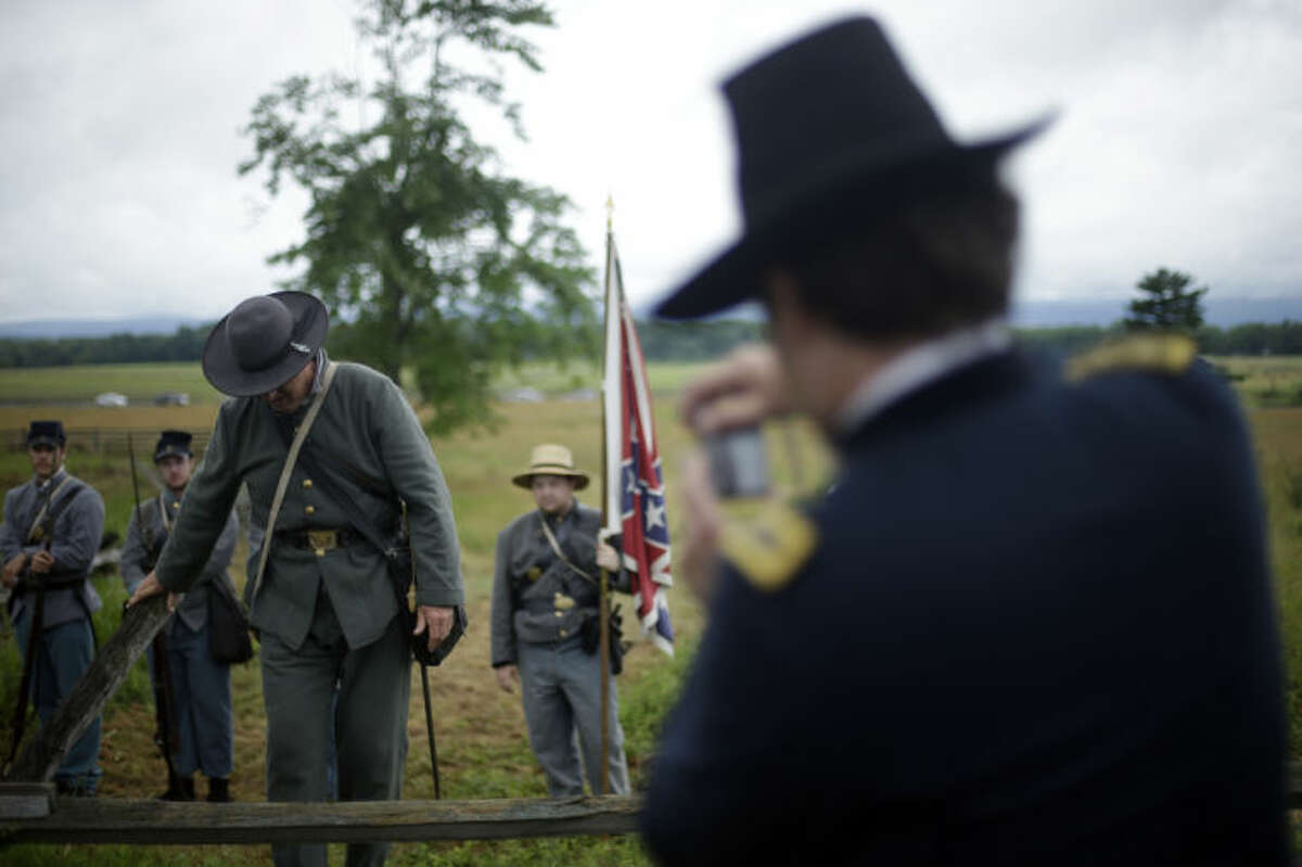 A Union re-enactor, right, photographs Confederate re-enactors crossing a wall held by Union forces at Gettysburg National Military Park ahead of a commemorative march where Pickett's Charge took place during ongoing activities commemorating the 150th anniversary of the Battle of Gettysburg, Wednesday, July 3, 2013, at in Gettysburg, Pa. Union forces turned away a Confederate advance in the pivotal battle of the Civil War fought July 1-3, 1863, which was also the war's bloodiest conflict with more than 51,000 casualties. (AP Photo/Matt Rourke)