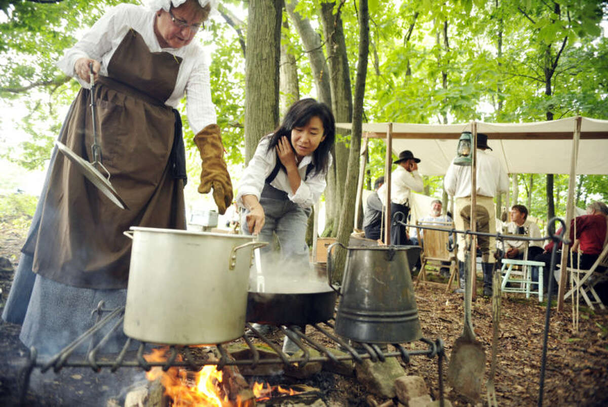 """Satomi Okada, 52, pulls her hair back as she transfers chicken thighs from a cast iron skillet to a soup pot under the guidance of re-enactor Candy Girard, 62 of Omaha, Neb., at the Blue Gray Alliance's re-enactment camp outside Gettysburg, Pa., on Friday, June 28, 2013. Okada, who is from Kobe, Japan, has a three-month tourist visa and is trying to learn what she can about the Civil War, which in Japan is called """"the North-South War."""" A Minnesota friend of hers is re-enacting, and invited her. Okada will be a """"powder monkey"""" - assisting with the cannons - with Terry's Texas Rangers Company H during the re-enactments. Some women did go to war - in cognito - with their brothers, fathers or husbands during the Civil War, and more than a few female re-enactors today are portraying that by abandoning the hoop skirts and petticoats in favor of men's wear and artillery. (AP Photo/York Daily Record, Chris Dunn)"""
