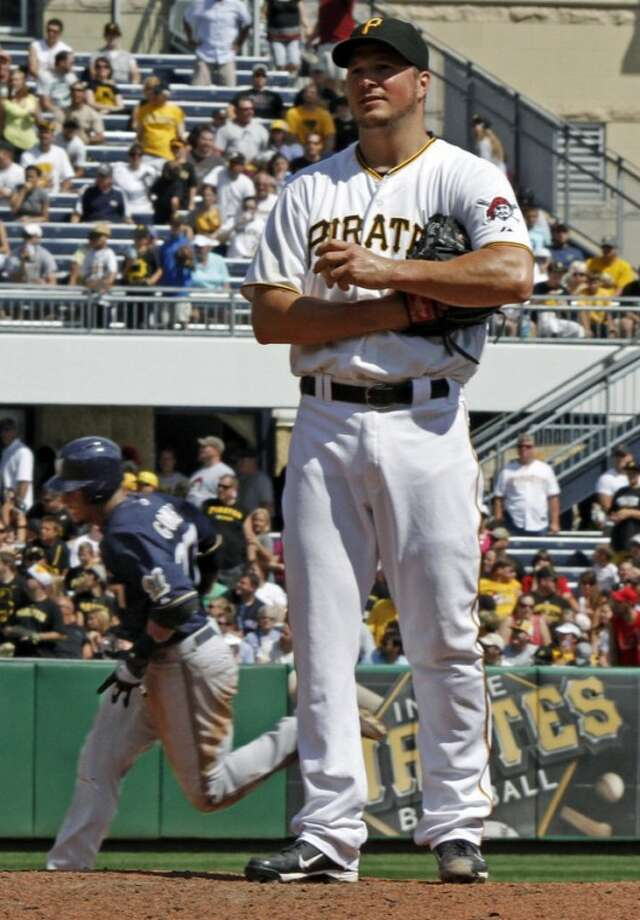 Pittsburgh Pirates starting pitcher Erik Bedard, right, stands on the mound as Milwaukee Brewers' Carlos Gomez rounds the bases behind him after hitting a three-run home run in the fourth inning of a baseball game, Sunday, Aug. 26, 2012, in Pittsburgh. (AP Photo/Keith Srakocic)