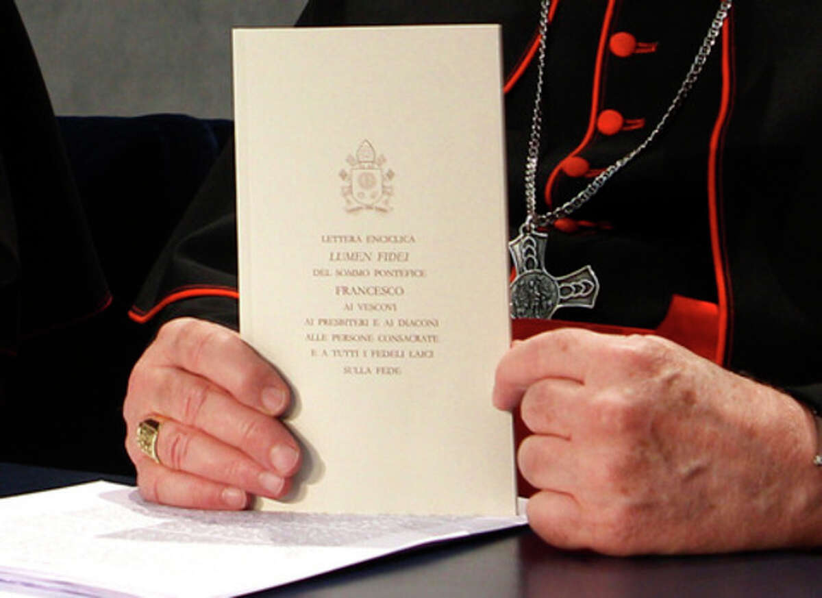 Cardinal Marc Ouellet shows a copy of the Pope Francis' Lumen Fidei encyclical letter prior to the start of a press conference for its presentation at the Vatican, Friday, July 5, 2013. Pope Francis issued his first encyclical Friday, a meditation on faith that is unique because it was written with someone else: Benedict XVI. Benedict's hand is evident throughout much of the first three chapters of