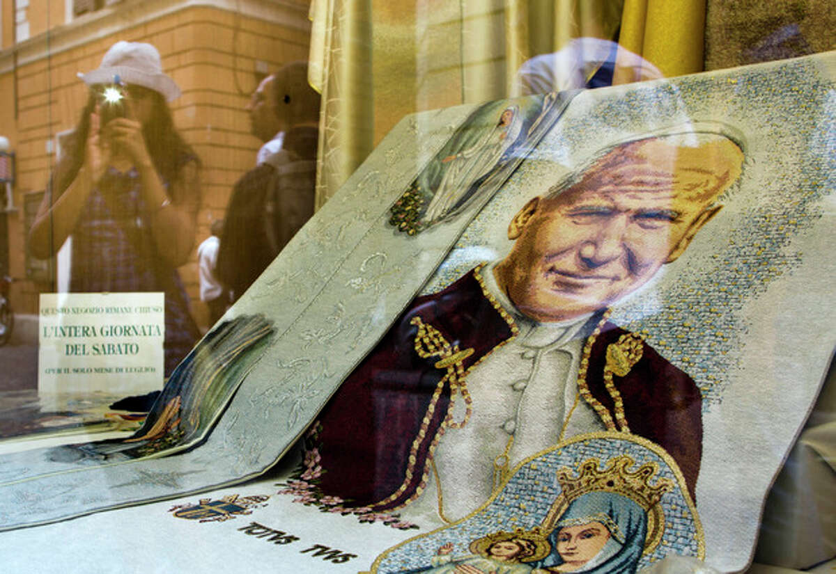 A girl uses her smartphone to take pictures of an embroidered drape depicting late Pope John Paul II on display in a downtown shop selling religious items, in Rome, Friday, July 5, 2013. Pope Francis decided Friday to make Pope John Paul II a saint, approving a miracle attributed to his intercession and setting up a remarkable dual canonization along with another beloved pope, John XXIII. (AP Photo/Domenico Stinellis)