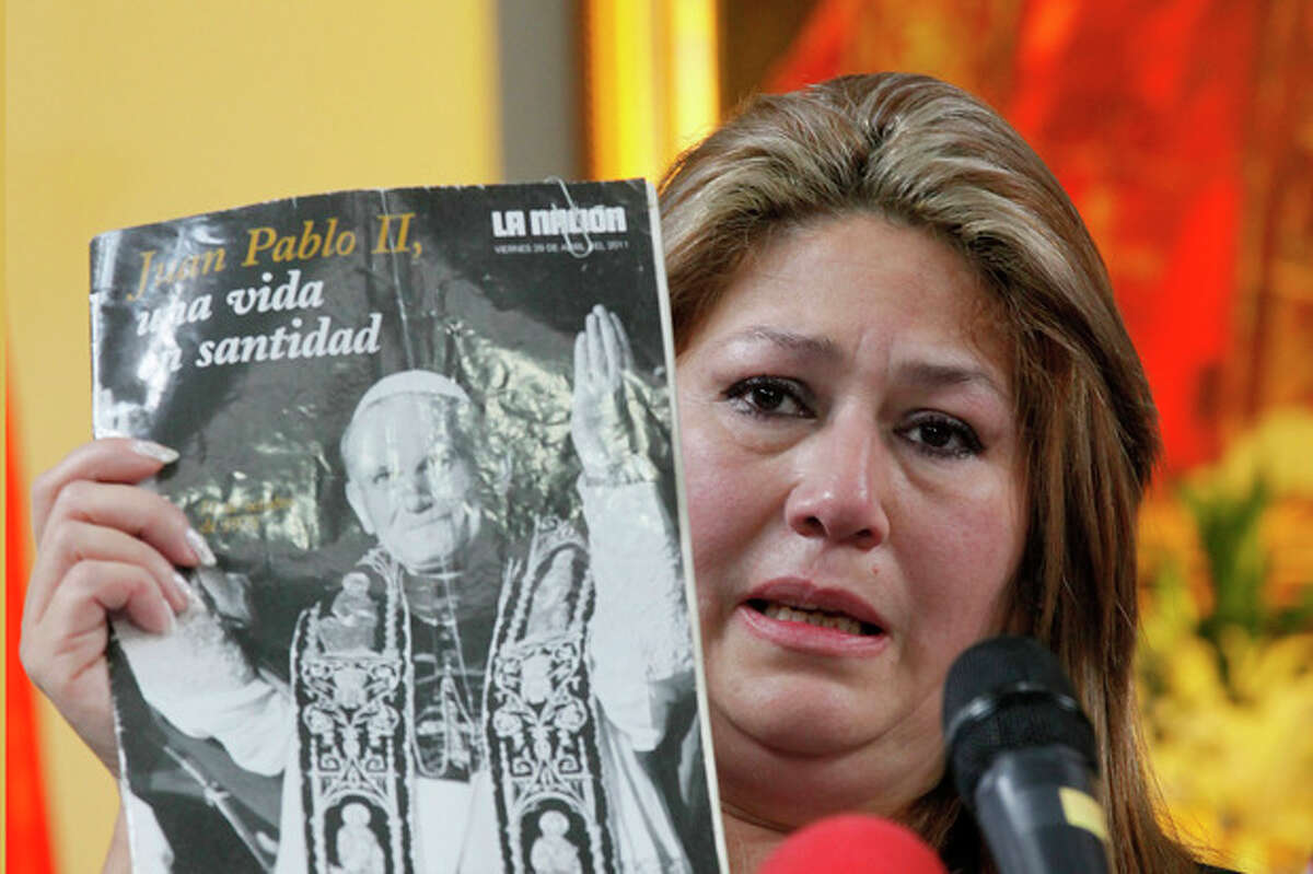 Costa Rica Floribeth Mora holds up a magazine featuring Pope John Paul II on the cover, as she gives her account of a miracle attributed to John Paul, during a press conference, at the Archbishop's office in San Jose, Costa Rica, Friday, July 5, 2013. Pope Francis on Friday approved the miracle of the Costa Rican woman bringing John Paul to the ranks of saints. Mora suffering from a cerebral aneurism and only given a month to live, was inexplicably cured on May 1, 2011, the date of John Paul's beatification, when millions of worshippers filled St. Peter's Square to honor the beloved Polish pontiff. (AP Photo/Enrigue Martinez)