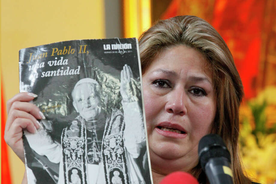 Costa Rica Floribeth Mora holds up a magazine featuring Pope John Paul II on the cover, as she gives her account of a miracle attributed to John Paul, during a press conference, at the Archbishop's office in San Jose, Costa Rica, Friday, July 5, 2013. Pope Francis on Friday approved the miracle of the Costa Rican woman bringing John Paul to the ranks of saints. Mora suffering from a cerebral aneurism and only given a month to live, was inexplicably cured on May 1, 2011, the date of John Paul's beatification, when millions of worshippers filled St. Peter's Square to honor the beloved Polish pontiff. (AP Photo/Enrigue Martinez) / AP