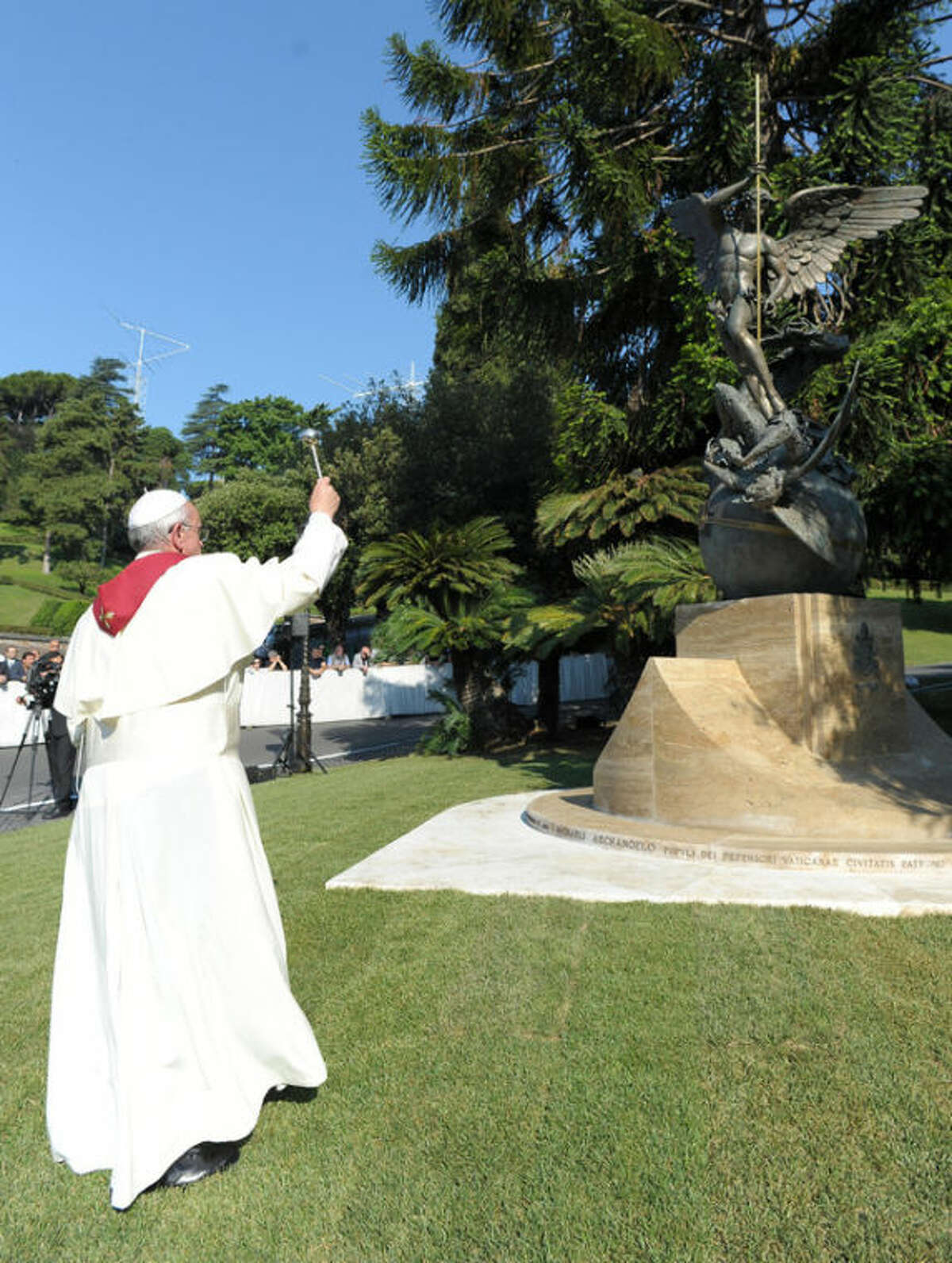 """In this photo provided by the Vatican newspaper L'Osservatore Romano Pope Francis blesses the San Michele Arcangelo statue during a ceremony for its unveiling at the Vatican, Friday, July 5, 2013. Francis and Pope emeritus Benedict XVI were together Friday morning for the inauguration of the new monument inside the Vatican gardens - the first time they have been seen together since May 2, when Francis welcomed Benedict back to the Vatican after his initial retirement getaway. Pope Francis issued his first encyclical Friday, a meditation on faith that is unique because it was written with Benedict XVI. Benedict's hand is evident throughout much of the first three chapters of """"The Light of Faith,"""" with his theological style, concerns and reference points clear. (AP Photo/L'Osservatore Romano, ho)"""