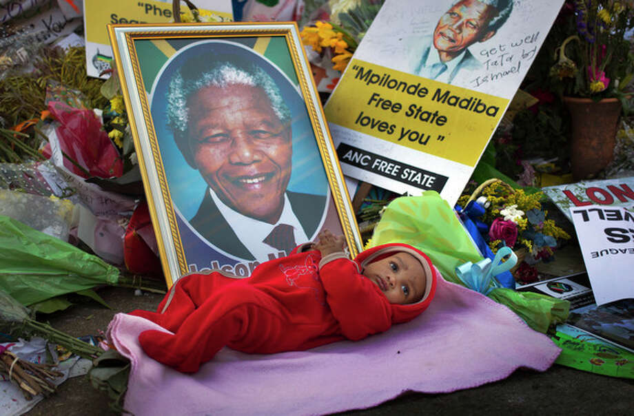 Oamohetswe Mabitsela, 4 months old, is placed by his mother next to a picture of Nelson Mandela for her to take a photograph of him with her camera phone, outside the Mediclinic Heart Hospital where former South African President Nelson Mandela is being treated in Pretoria, South Africa Thursday, July 4, 2013. The remains of Nelson Mandela's three deceased children were reburied at their original resting site on Thursday, a day after a court ordered their return two years after Mandela's grandson moved the bodies. (AP Photo/Ben Curtis) / AP