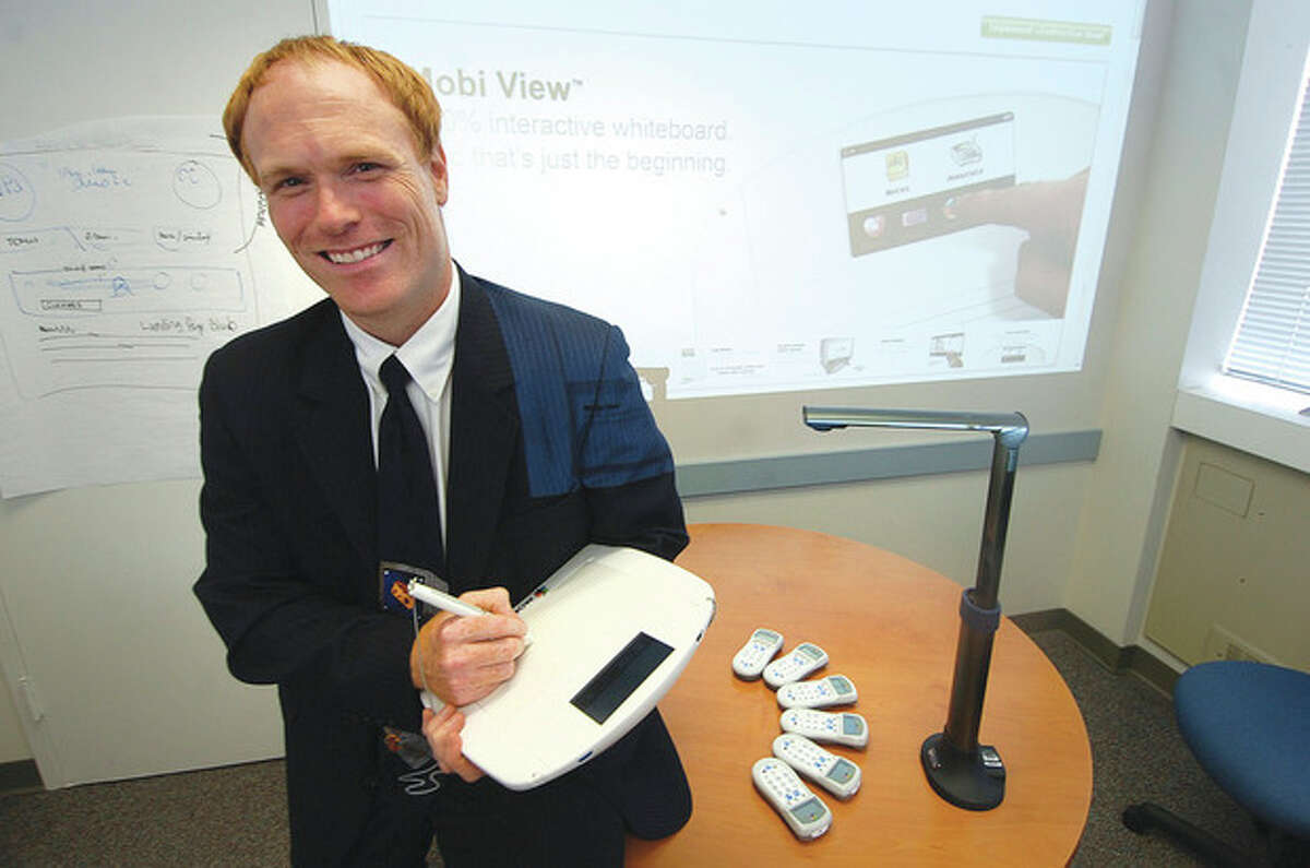 Hour photo / Alex von Kleydorff Robert Polselli Jr., director of Technology for Norwalk Public Schools, holds the Mobi unit. Next to him are the CPS Clickers and the Hoover cam.
