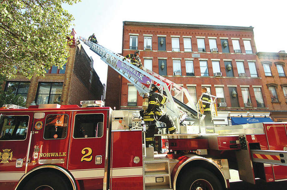 Hour Photo/ Alex von Kleydorff. Firefighters descened down to Ladder Truck 2 after investigating a report of smoke from the roof top of Match restaurant in SONO on Tuesday afternoon / 2012 The Hour Newspapers