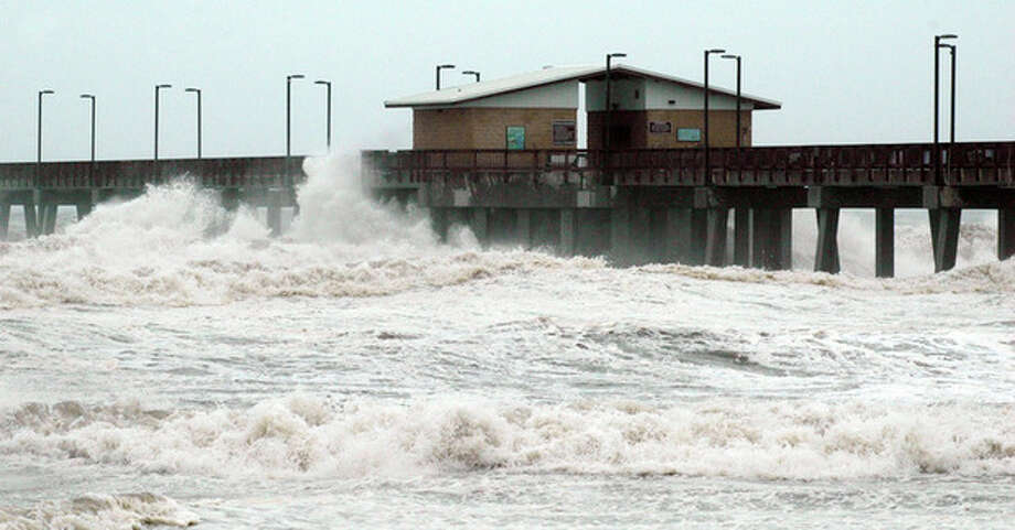 Waves crash into the public fishing pier at Gulf State Park in Gulf Shores, Ala., shortly before Hurricane Isaac made landfall in Louisiana on Tuesday, Aug. 28, 2012. Crews removed flooring panels from the pier to prevent damage. (AP Photo/Jay Reeves) / AP