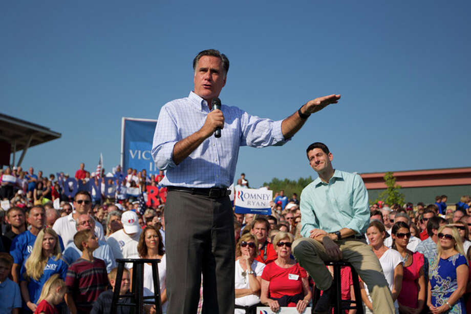 In this Aug. 25, 2012, photo, Republican presidential candidate, former Massachusetts Gov. Mitt Romney speaks as vice presidential running mate Rep. Paul Ryan, R-Wis., listens during a campaign rally in Powell, Ohio. Romney and Ryan are the political world's newest odd couple. They're bound by substance, but dramatically different in their styles. The running mates share a love of policy, and a fascination with the world's economy and America's place in it. But where Romney is buttoned-up and reserved on the campaign trail, Ryan is relaxed and exudes a natural enthusiasm. (AP Photo/Evan Vucci) / AP