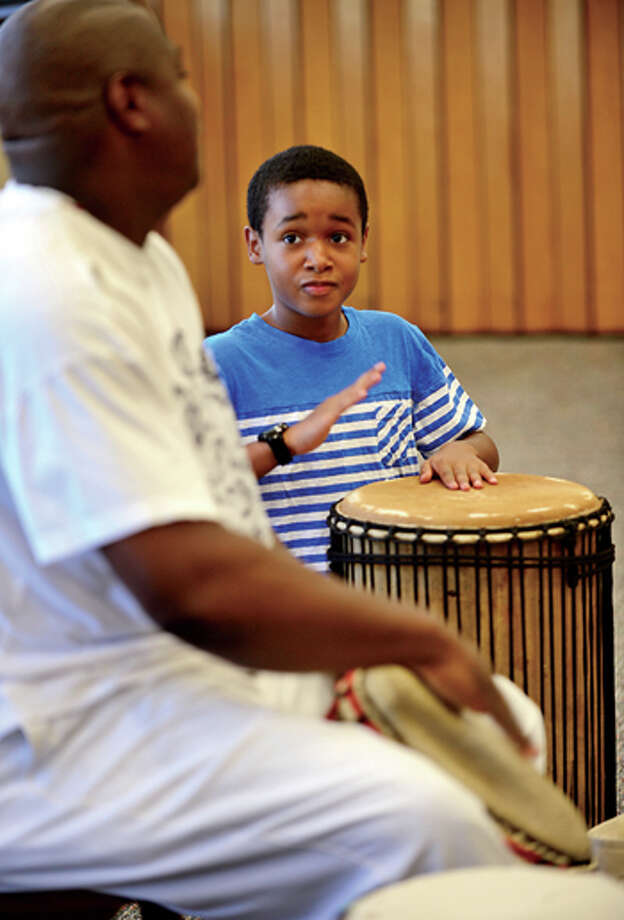 Christian Tapper, 10, drums along with Henry Jones of the Infinite Roots drum troupe at the Norwalk Public Library Friday. Hour photo / Erik Trautmann / (C)2013, The Hour Newspapers, all rights reserved