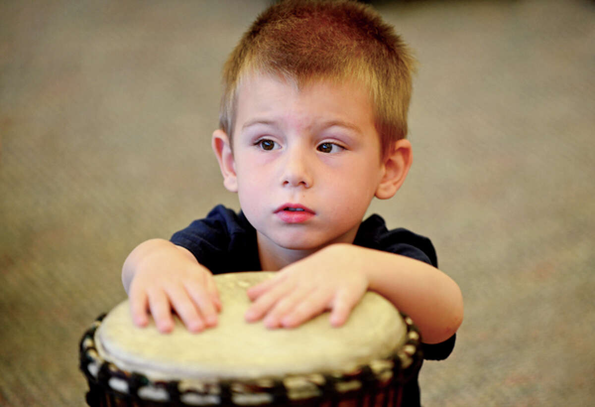 Lucas Lewertoff, 4, drums along with Henry Jones of the Infinite Roots drum troupe at the Norwalk Public Library Friday. Hour photo / Erik Trautmann