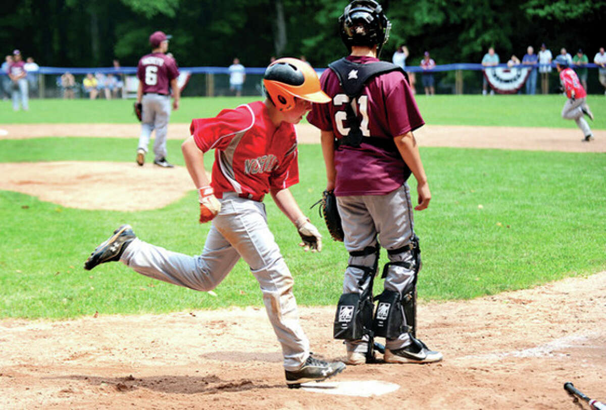 Jimmy Evans crosses the plate for Norwalk LL in their playoff game against Stamford National at Chesnut Hill Park in Stamford Saturday. Hour photo / Erik Trautmann