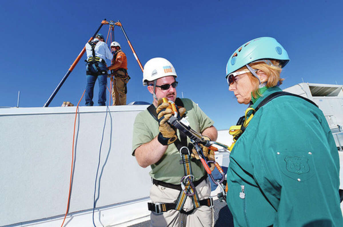 Stamford Superintendent of Schools, Winifred Hamilton, prepares to join the Over the Edge event and rappel down one of Stamford's tallest buildings, the new Infinity building at Harbor Point, to support Special Olympics athletes. Hour photo / Erik Trautmann