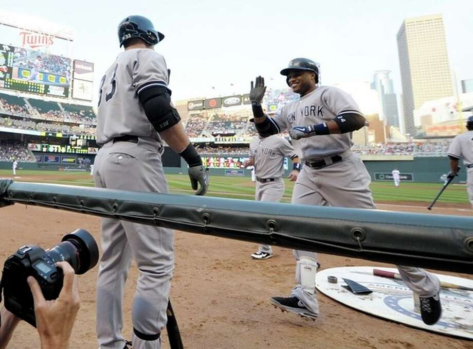 New York Yankees' Robinson Cano, right, is all smiles as he reaches the dugout after his second home run of the game in the third inning of a baseball game, Monday, July 1, 2013 in Minneapolis. (AP Photo/Jim Mone) / AP