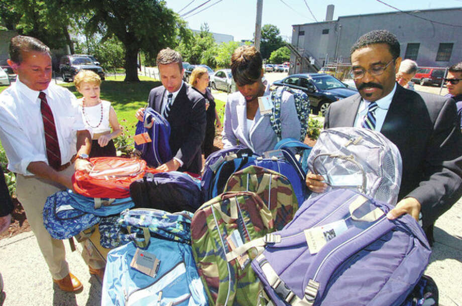 Hour photo / Alex von KleydorffFrom the left, Rob Werner, running for state rep. in Darien; Sen. Bob Duff, D-25, DTC Party Chairman Amanda Brown and state Rep. Bruce Morris, D-140, sort backpacks the DTC is donating to the Carver Center and NEON. / 2012 The Hour Newspapers