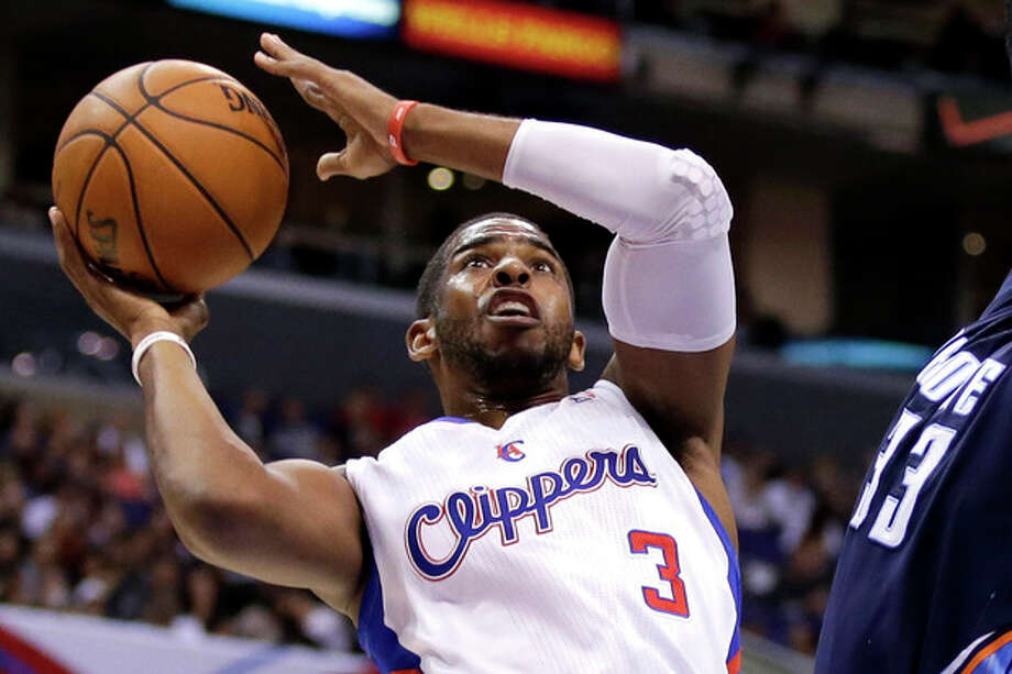 FILE - In this Feb. 27, 2013 file photo, Los Angeles Clippers guard Chris Paul plays against the Charlotte Bobcats during an NBA basketball game in Los Angeles. Paul is staying with the Clippers. The All-Star point guard agreed to a new deal on the first day free agency opened, agent Leon Rose confirms, Monday July 1, 2013. (AP Photo/Chris Carlson) / AP