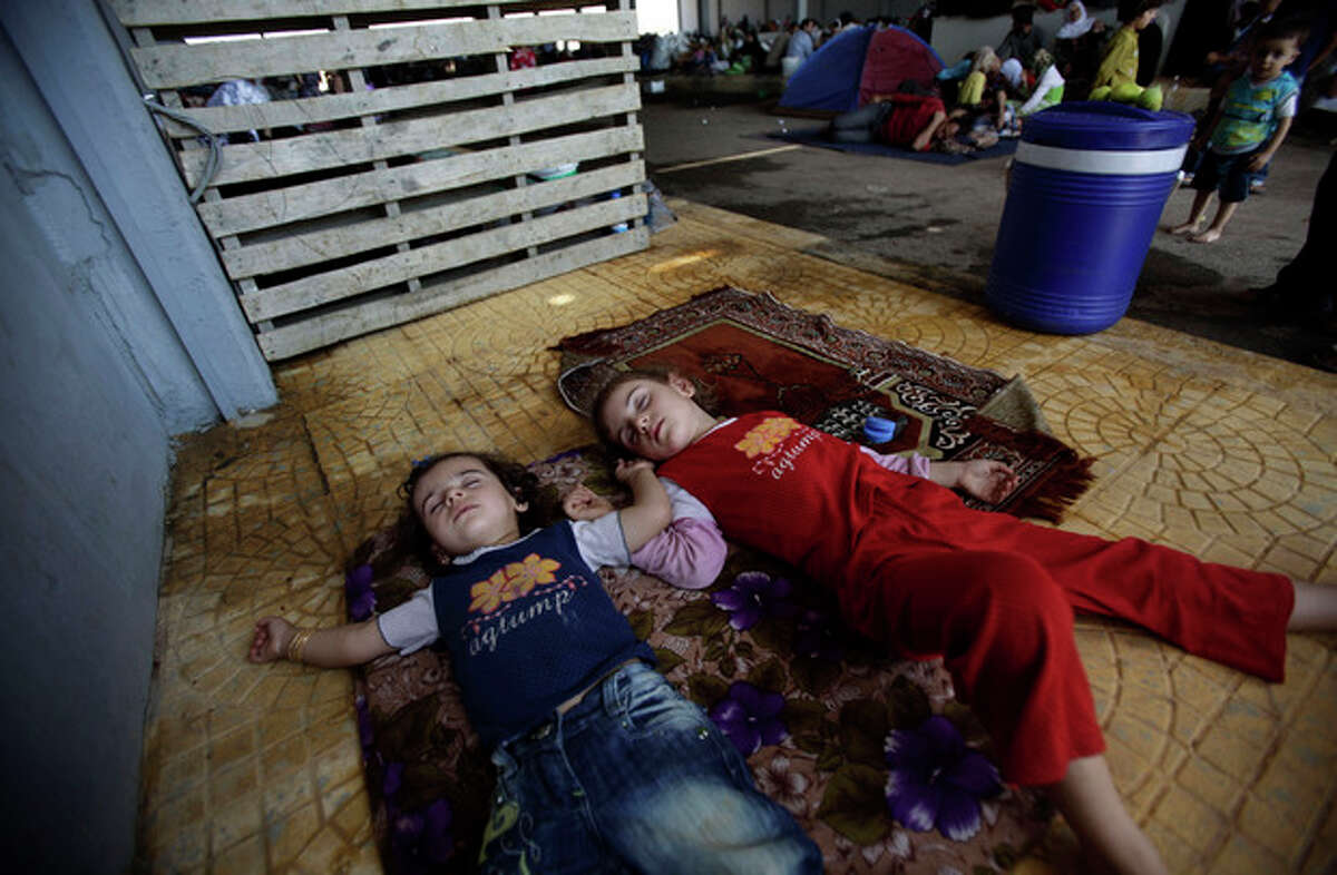 Syrian girls, who fled their home with their family in Aleppo, due to fighting between the Syrian army and the rebels, sleep on teh ground, as their family take refuge at the Bab Al-Salameh border crossing, in hopes of entering one of the refugee camps in Turkey, near the Syrian town of Azaz, Wednesday, Aug. 29, 2012. (AP Photo/Muhammed Muheisen)