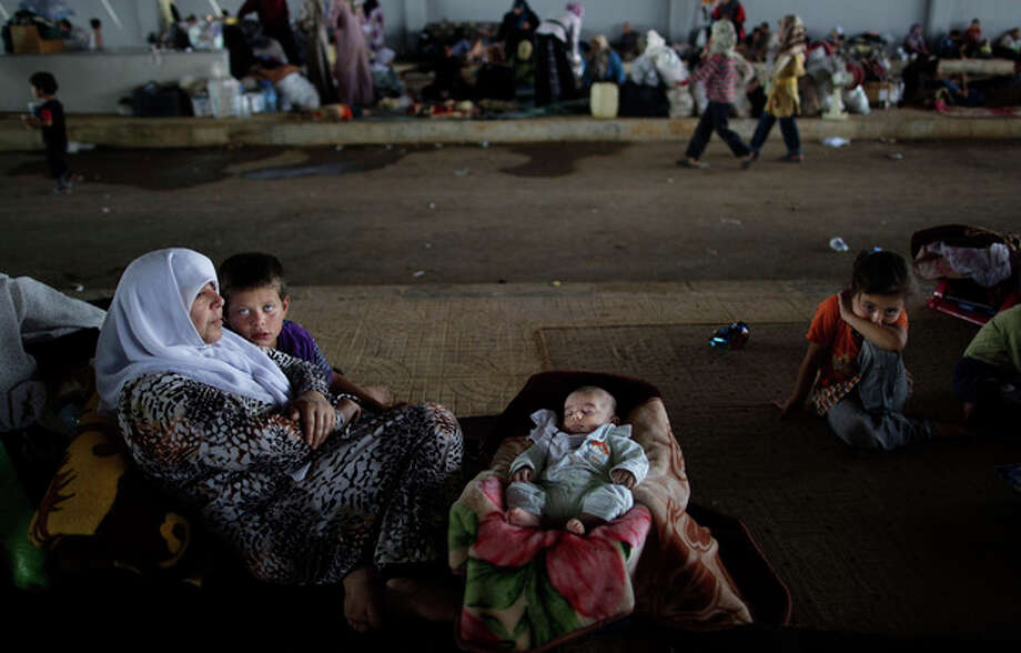 A Syrian family, who fled their home, due to fighting between the Syrian army and the rebels, take refuge at the Bab Al-Salameh border crossing, in hopes of entering one of the refugee camps in Turkey, near the Syrian town of Azaz, Wednesday, Aug. 29, 2012. (AP Photo/Muhammed Muheisen) / AP