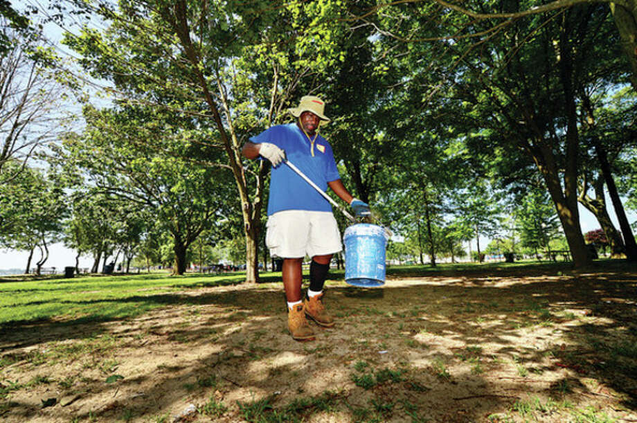 Recreation and Parks worker Al Howard picks up bits of trash at Shady Beach Friday following the independence Day holiday. Last year there were complaints about the Recreation and Parks Department slow respose to trash clean up.Hour photo / Erik Trautmann / (C)2013, The Hour Newspapers, all rights reserved