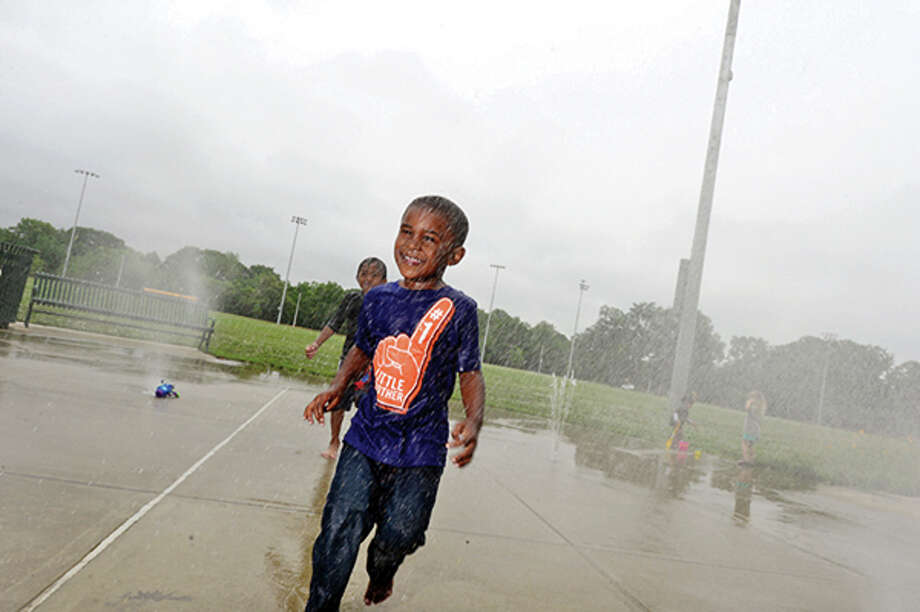 3 year old Ayden Derisier plays on the new spash pad on Thursday when the renovated Scalzi Park was officially reopened. Hour photo / Erik Trautmann / (C)2013, The Hour Newspapers, all rights reserved