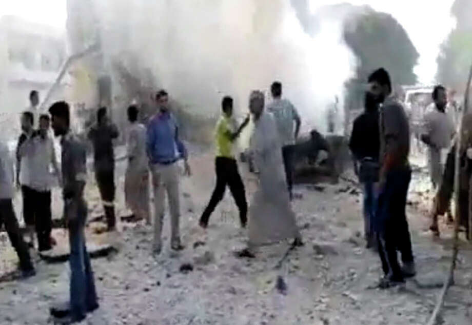 In this image made from amateur video released by the Shaam News Network and accessed Tuesday, Aug. 28, 2012, Syrian men stand near smoke rising from buildings due to shelling in Kfarnebel, Idlib province, northern Syria. (AP Photo/Shaam News Network via AP video) THE ASSOCIATED PRESS IS UNABLE TO INDEPENDENTLY VERIFY THE AUTHENTICITY, CONTENT, LOCATION OR DATE OF THIS HANDOUT PHOTO / Shaam News Network
