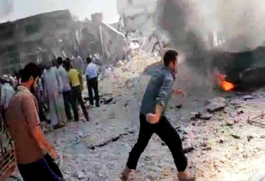 In this image made from amateur video released by the Shaam News Network and accessed Tuesday, Aug. 28, 2012, Syrian men stand near a burning car due to shelling in Kfarnebel, Idlib province, northern Syria. (AP Photo/Shaam News Network via AP video) THE ASSOCIATED PRESS IS UNABLE TO INDEPENDENTLY VERIFY THE AUTHENTICITY, CONTENT, LOCATION OR DATE OF THIS HANDOUT PHOTO / Shaam News Network
