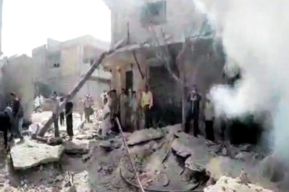 In this image made from amateur video released by the Shaam News Network and accessed Tuesday, Aug. 28, 2012, Syrian men stand in the rubble of a destroyed building from purported airstrikes in Kfarnebel, Idlib province, northern Syria. (AP Photo/Shaam News Network via AP video) THE ASSOCIATED PRESS IS UNABLE TO INDEPENDENTLY VERIFY THE AUTHENTICITY, CONTENT, LOCATION OR DATE OF THIS HANDOUT PHOTO / Shaam News Network