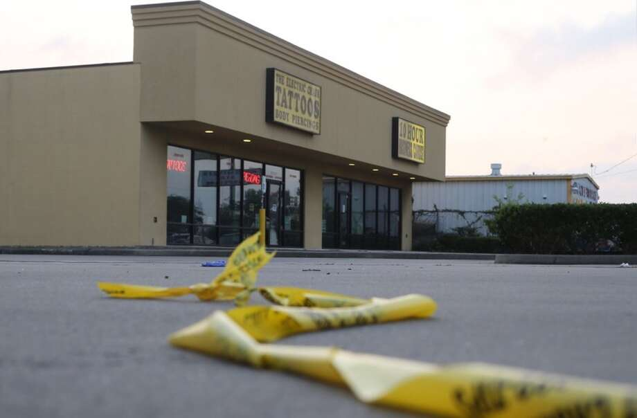 A police tape remains outside The Electric Chair Tattoos on Richmond in Houston where a man was shot on Tuesday, June 14, 2016. Photo: Elizabeth Conley