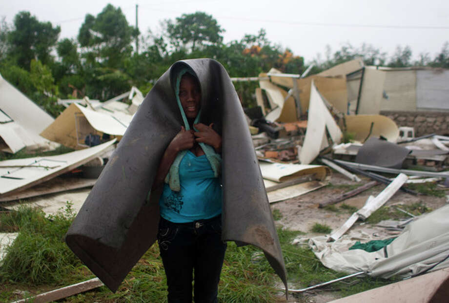 A woman covers herself with what's left of her home in a camp set up for people displaced by the 2010 earthquake that was destroyed by Tropical Storm Isaac in Port-au-Prince, Haiti, Saturday Aug. 25, 2012. Tropical Storm Isaac swept across Haiti's southern peninsula early Saturday, dousing a capital city prone to flooding and adding to the misery of a poor nation still trying to recover from the 2010 earthquake. (AP Photo/Dieu Nalio Chery) / AP