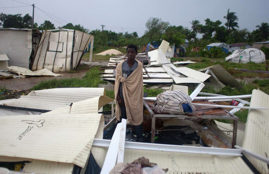 A man stands next to his bed after Tropical Storm Isaac destroyed his home and others at a camp set up for people displaced by the 2010 earthquake in Port-au-Prince, Haiti, Saturday, Aug. 25, 2012. Tropical Storm Isaac swept across Haiti's southern peninsula early Saturday, dousing a capital city prone to flooding and adding to the misery of a poor nation still trying to recover from the 2010 earthquake. (AP Photo/Dieu Nalio Chery) / AP