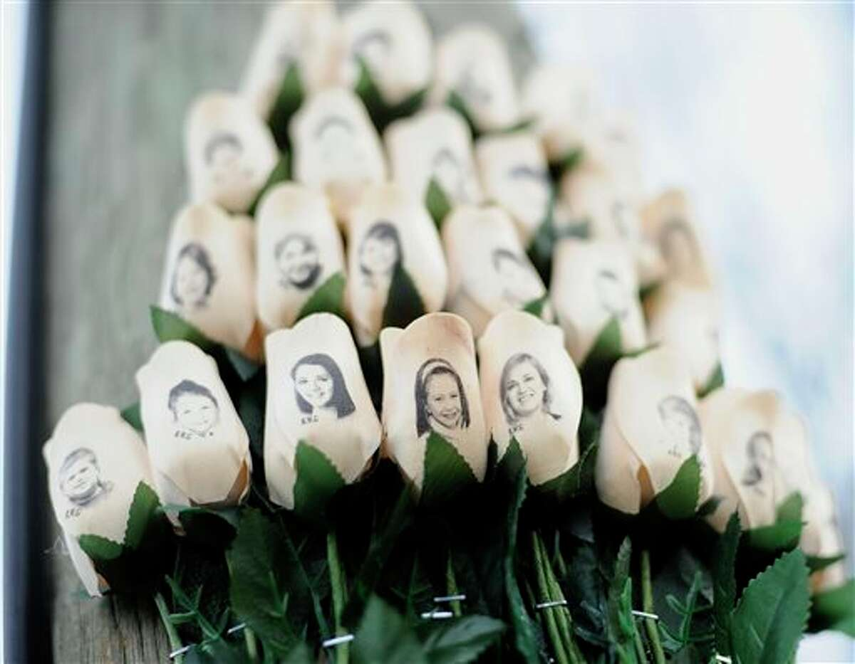 FILE - In this Jan. 14, 2013 file photo, white roses with the faces of victims of the Sandy Hook Elementary School shooting are attached to a telephone pole near the school on the one-month anniversary of the shooting that left 26 dead in Newtown, Conn. Some Newtown families have said they were given a voice late in the process of dispersing the millions of dollars in donated funds, and that the process has been bureaucratic, difficult, unpleasant, and has added to their pain. (AP Photo/Jessica Hill, File)